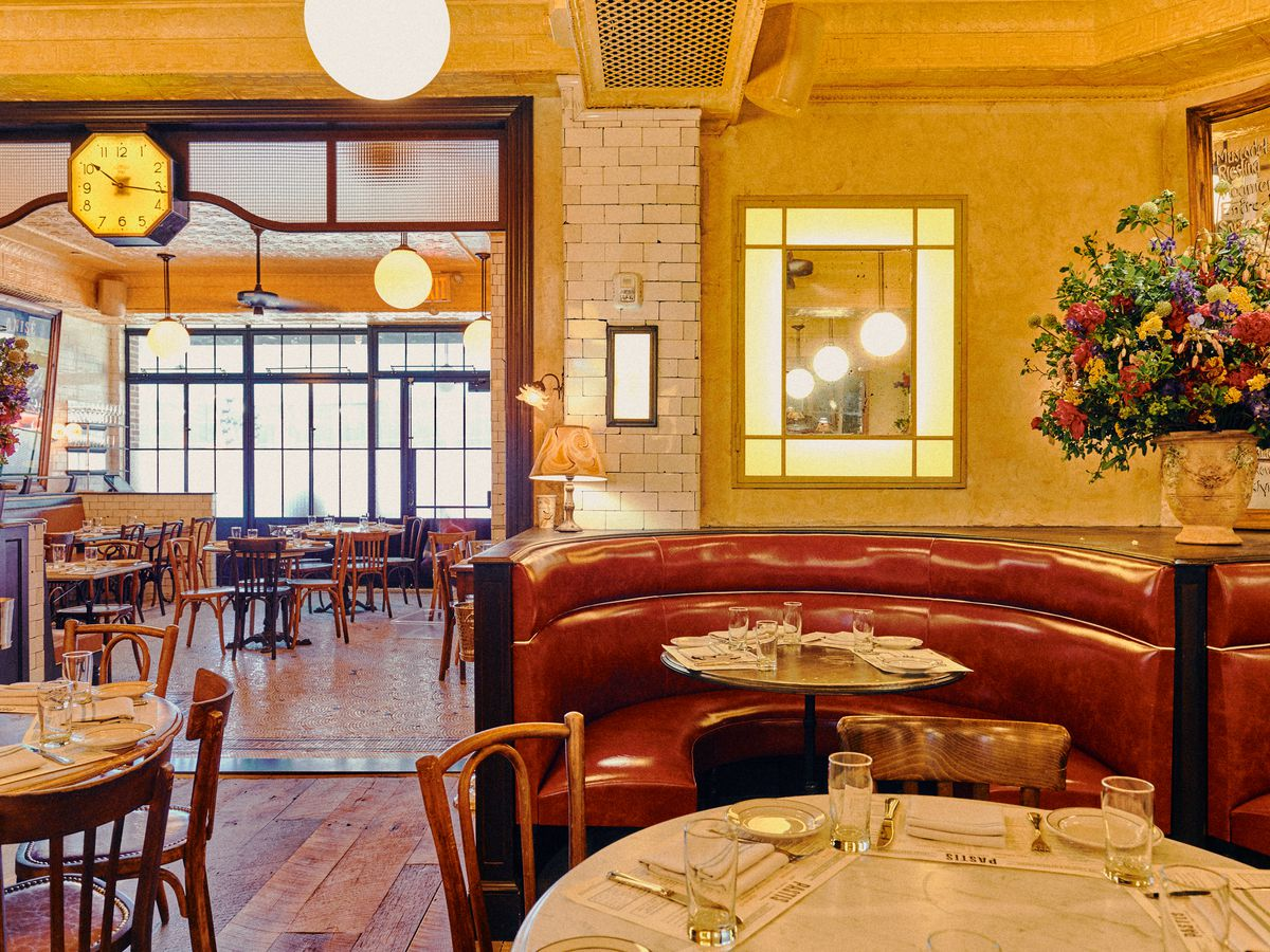 A leather u-shaped booth in a naturally lit dining room with hardwood floors
