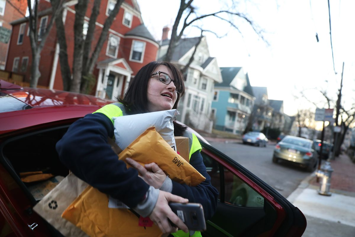 A woman gets out of her car with her arms full of packages.