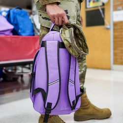 Air Force 2nd Lt. Will Fuentes carries a purple backpack as free school supplies are distributed during Operation Homefront's annual Back-to-School Brigade event at Hill Field Elementary in Clearfield on Tuesday, Aug. 13, 2019.
