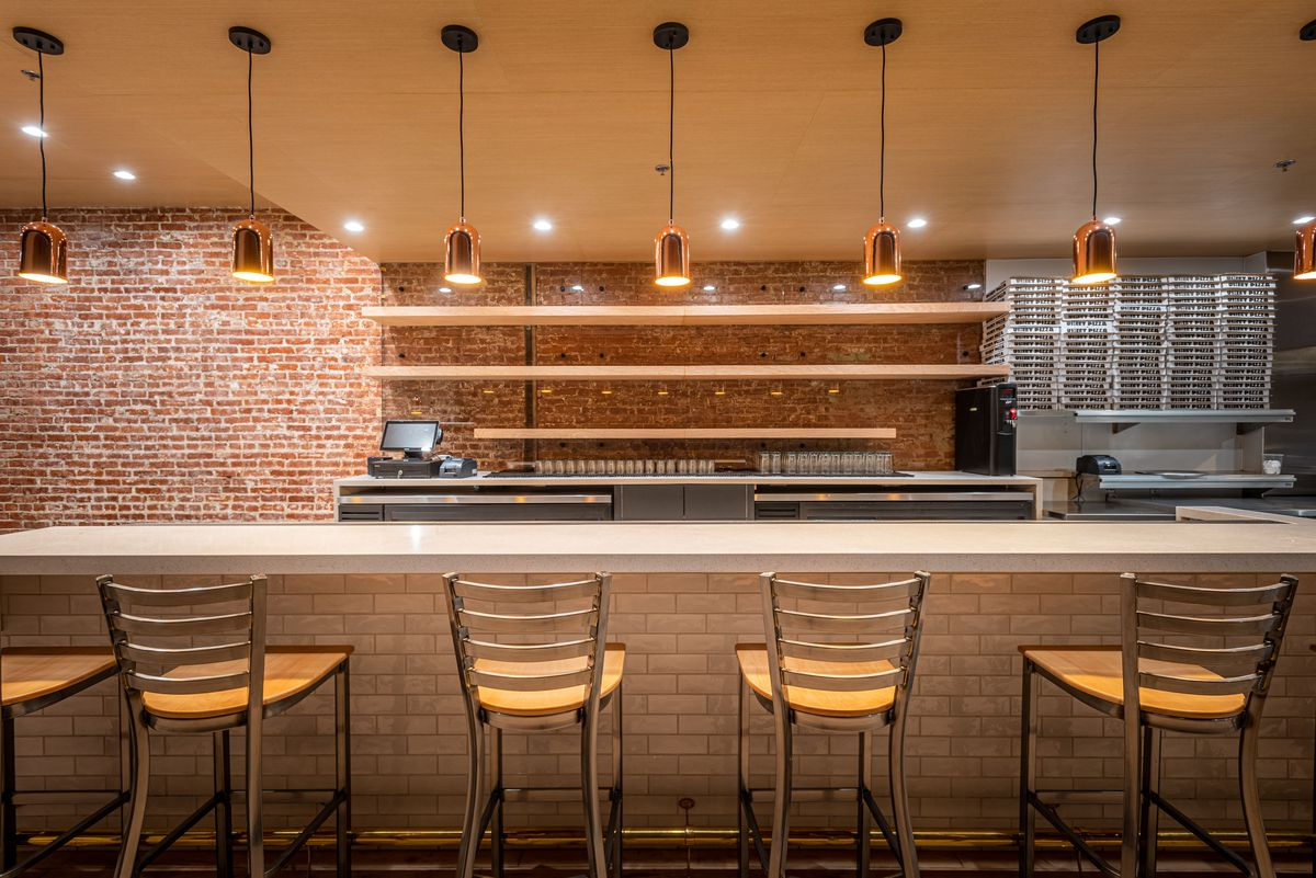 Stools set for dining at a bar area inside of a new restaurant.