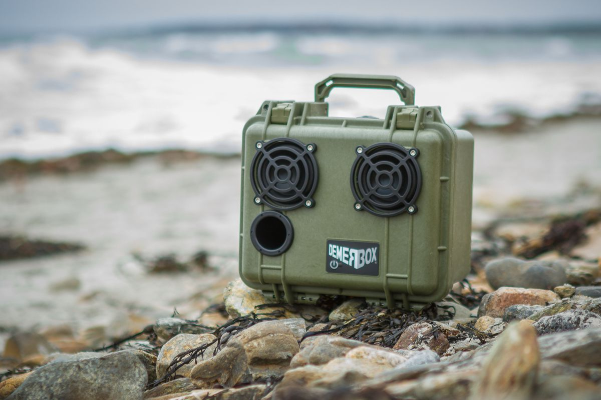 A green portable bluetooth speaker. The word Demerbox is on a label on the front of the speaker. The speaker is perched on top of small rocks.