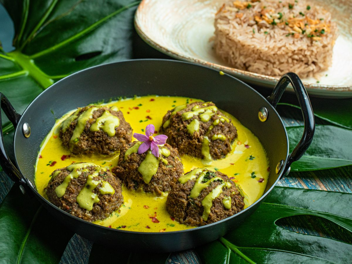 Five meatballs in a yellow sauce arranged in a black dish with handles with a scoop of rice on a dish in the background. The plates are sitting on a bed of green leaves.