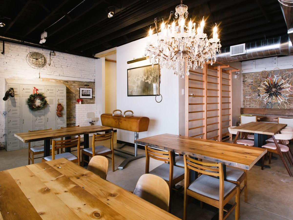 A well-lit room with chandelier and wood tables.