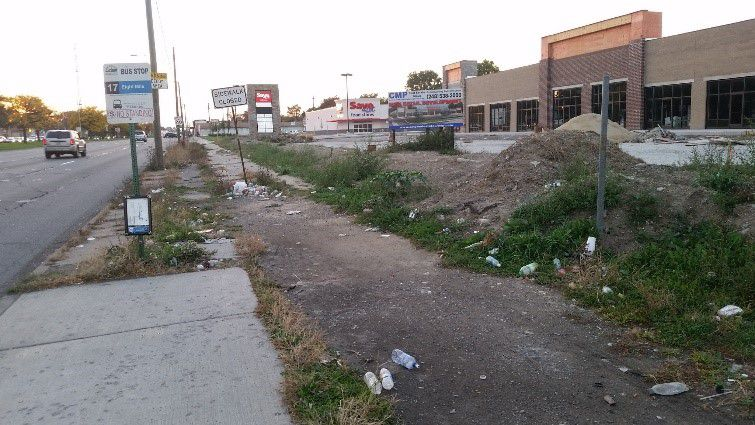 A sidewalk in Detroit. Part of the sidewalk is dirt and the other part is concrete. There are buildings adjacent to the sidewalk.