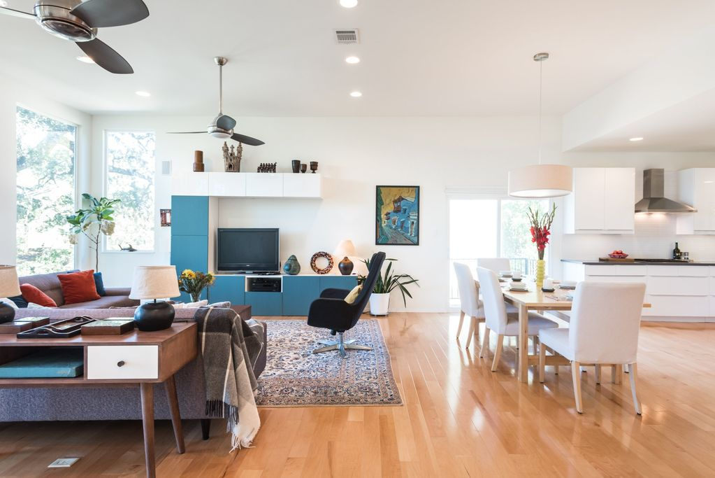 A living area with a table, chairs, couches, shelves, an area rug, and hardwood floors.