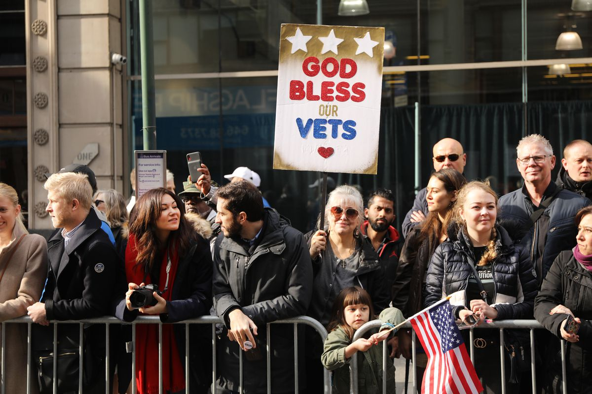 """Onlookers at the Veterans Day Parade in New York City stand behind a barricade. One holds a sign that reads """"God bless our vets."""""""