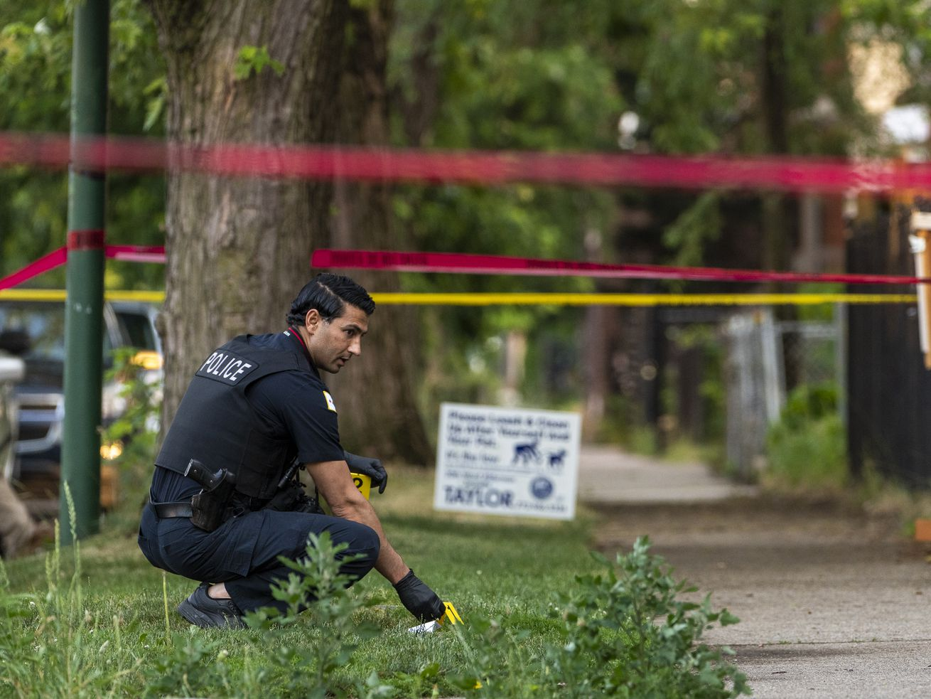 Chicago police work the scene where a 14-year-old boy was critically wounded in a shooting in the 6500 block of South Champlain Ave, in the West Woodlawn neighborhood, Saturday, June 12, 2021.