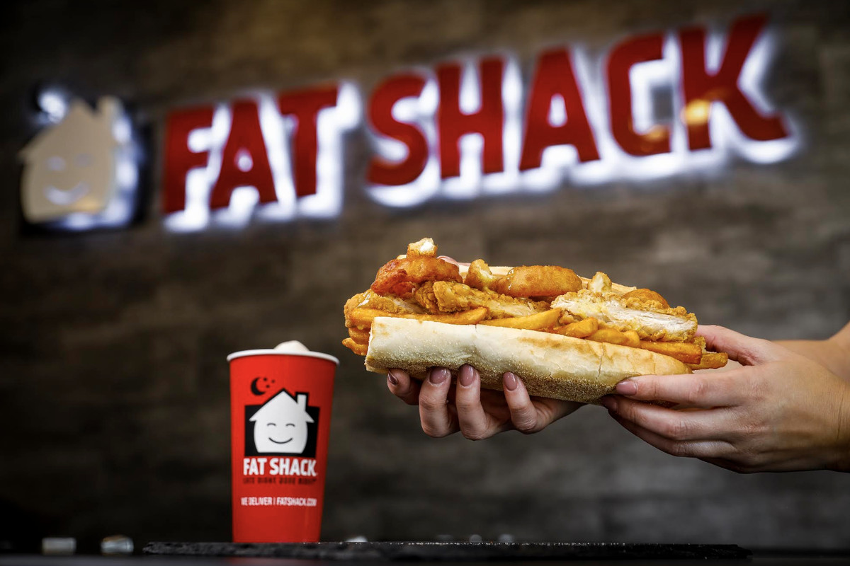 A sandwich stuffed with chicken tenders and fries, next to a Fat Shack cup, with the Fat Shack logo lit up on a brick wall in the background.
