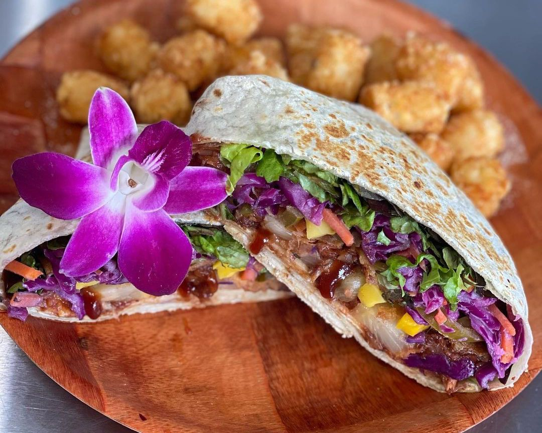 A photo of the vegan crunch wrap at Sharks Cove with a flower and tater tots