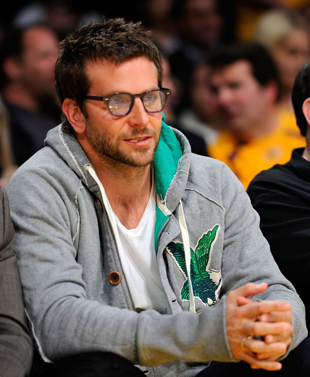 Bradley Cooper wearing a gray hoodie with a green eagle at a Lakers game in 2010
