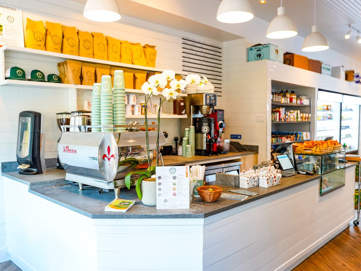 A naturally lit cafe space lined with yellow bags of coffee, an espresso machine, a curved white countertop, and a display case filled with pastries
