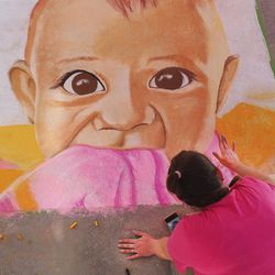 Lexi Daley works on her chalk art of her son Max during the fourth year of Chalk the Walk in West Jordan on Saturday, Sept. 5, 2020. The County Library welcomed chalk artists and their fans to participate in the library's first in-person event since COVID-19 measures went into effect in March.