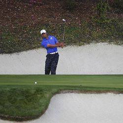 Tiger Woods watches his chip shot on the 12th green during a practice round for the Masters golf tournament Monday, April 2, 2012, in Augusta, Ga.