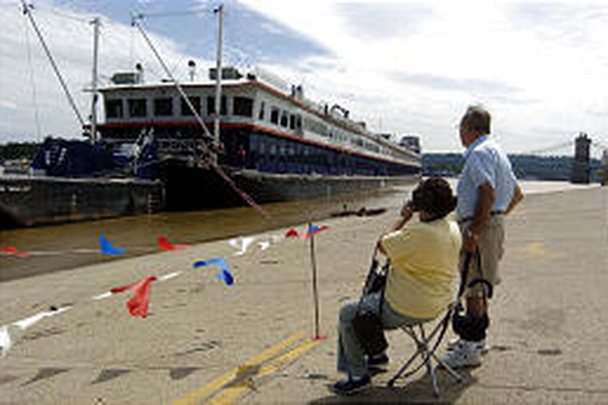 Dean and Carol Dubois watch the River Explorer cruise boat as it docks at the public landing in downtown Cincinnati. They traveled on the boat the next day.