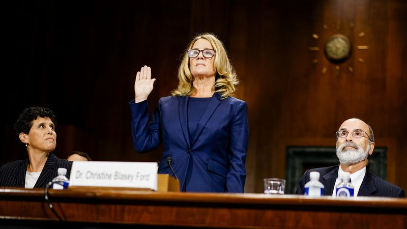 Christine Blasey Ford holds up her right hand to be sworn in at a Senate Judiciary Committee.