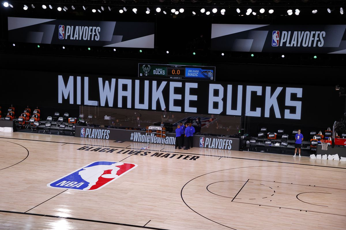 Referees huddle on an empty court at game time of a scheduled game between the Milwaukee Bucks and the Orlando Magic.