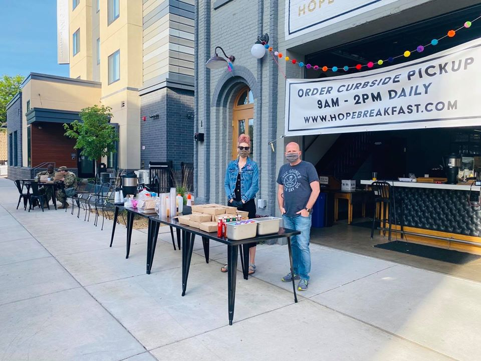 Two people stand outside Hope, in front of a table