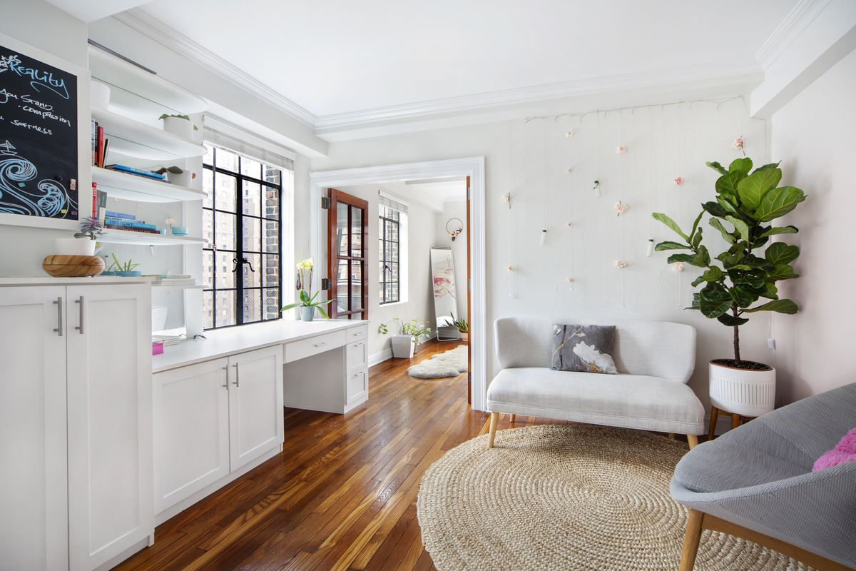 A white living area with casement windows and white built-in cabinets on the east wall.