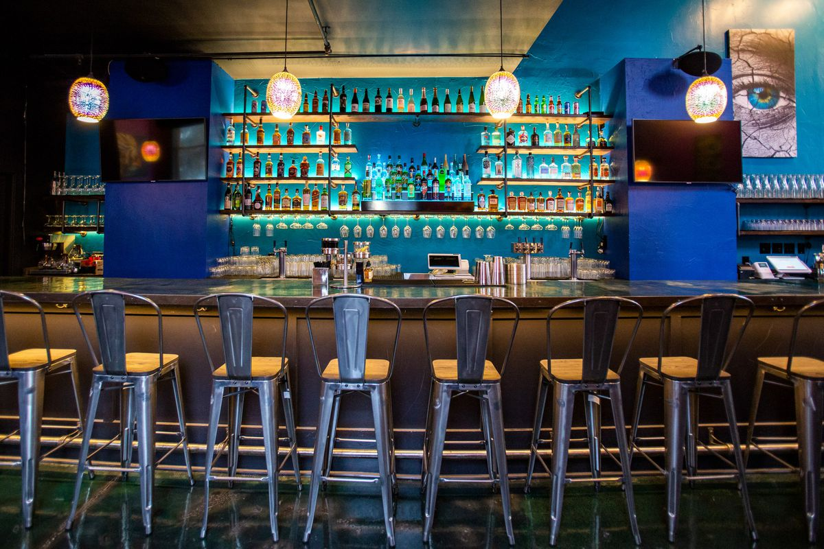 A look at the blue backlit bar at Zaika, with empty chairs, rows of bottles, two TVs, and a painting to the right of a human eye.