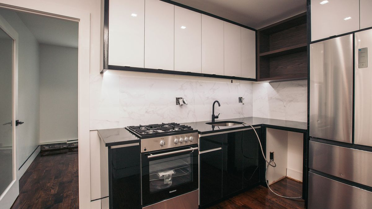 A kitchen with white and wooden cabinetry.
