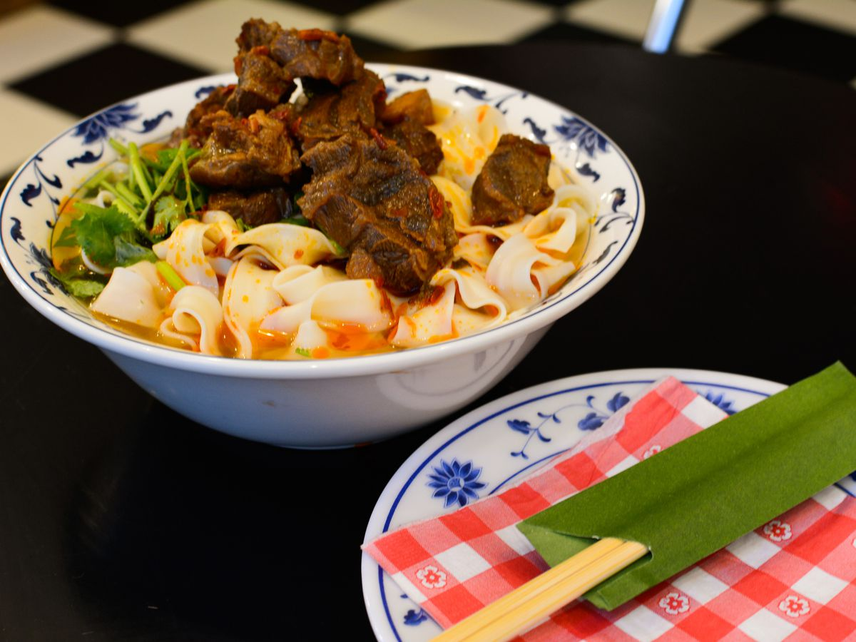 A bowl and a plate are placed on a dark table. The bowl has thick noodles and pieces of beef. The plate has chopsticks.