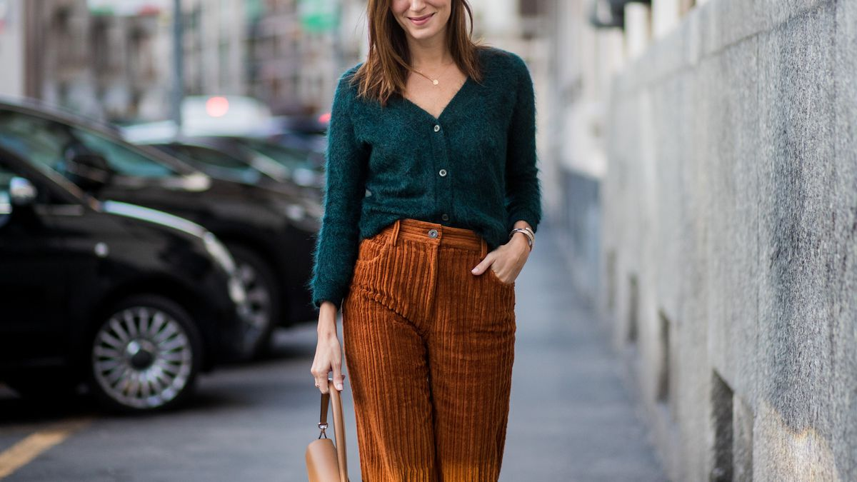 A woman in brown corduroys and a green sweater walking on the street