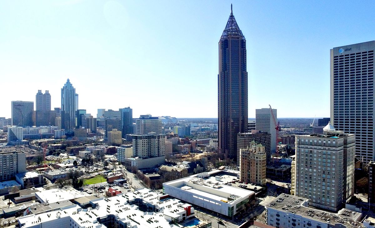 A drone's image of the Atlanta skyline set against a clear blue backdrop of the sky.