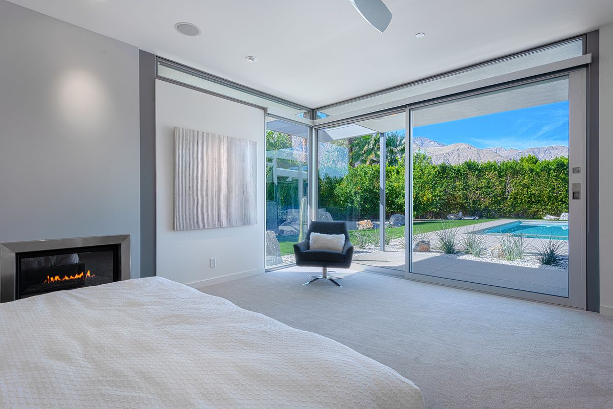 A sleek bedroom has gray walls, a white bed, a single chair, and walls of glass that look out onto a pool.