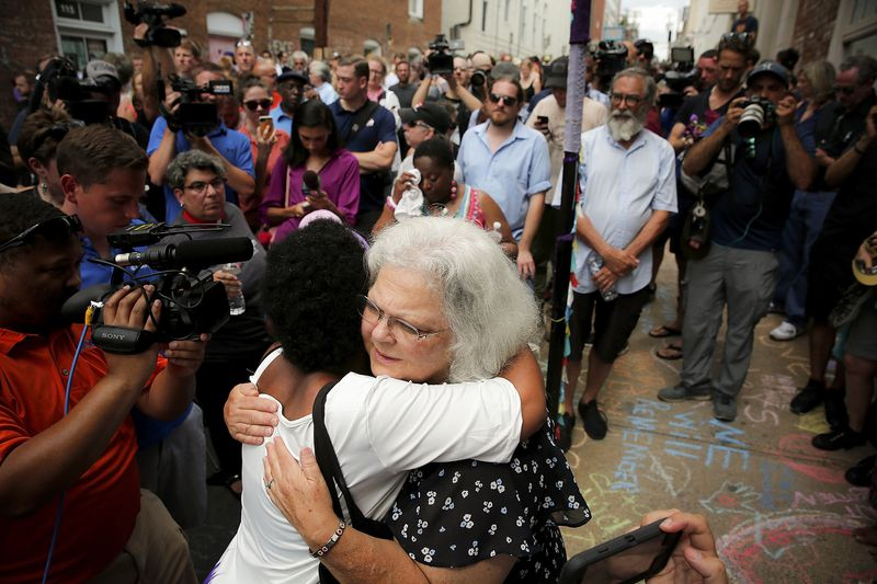 Susan Bro (center), mother of Heather Heyer, hugs a young woman near a makeshift memorial for her daughter in Charlottesville, VA.