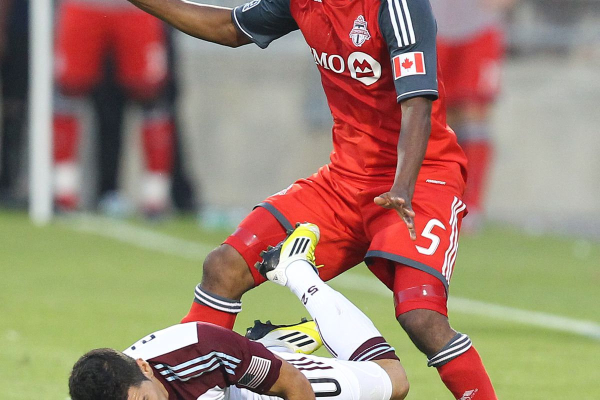 TORONTO, CANADA - JULY 18: Ashtone Morgan #5 of Toronto FC knocks down Martin Rivero #10 of the Colorado Rapids during MLS action at the BMO Field July 18, 2012 in Toronto, Ontario, Canada.  (Photo by Abelimages/Getty Images)
