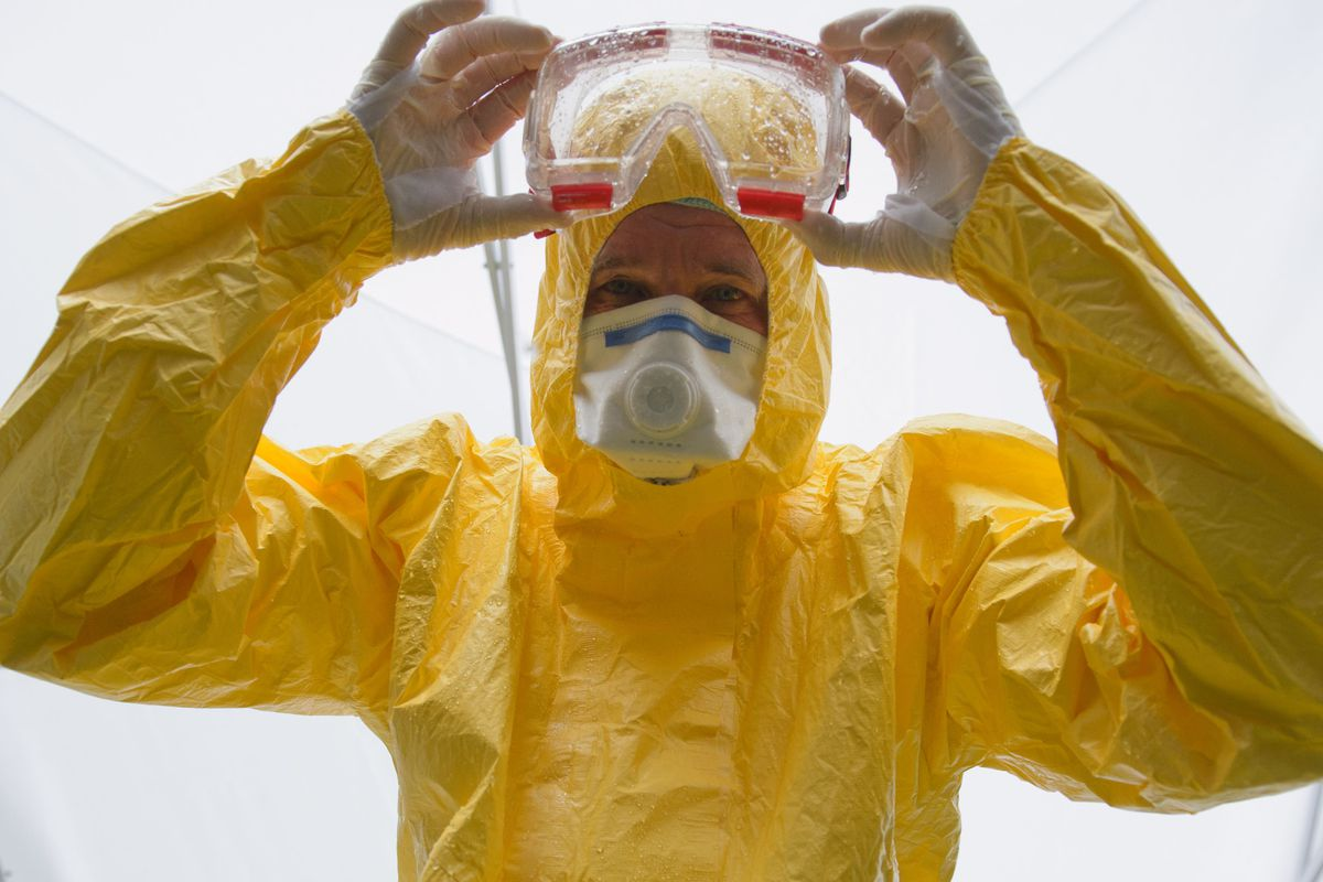 A volunteer doctor who will travel to West Africa to help care for Ebola patients in one of the protective suits that have become a symbol of this outbreak.