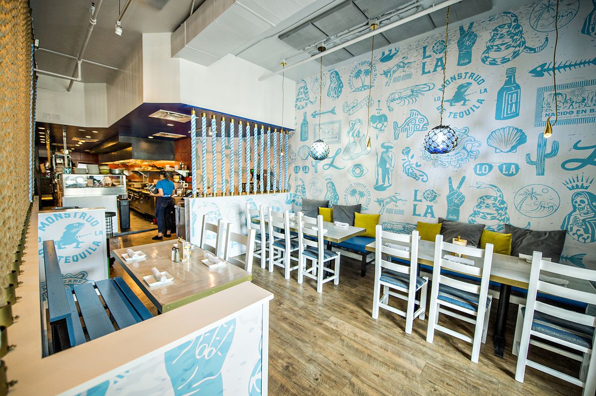 Four- and six-top tables have a view into the kitchen toward the right of the dining room at Lola Coastal Mexican.