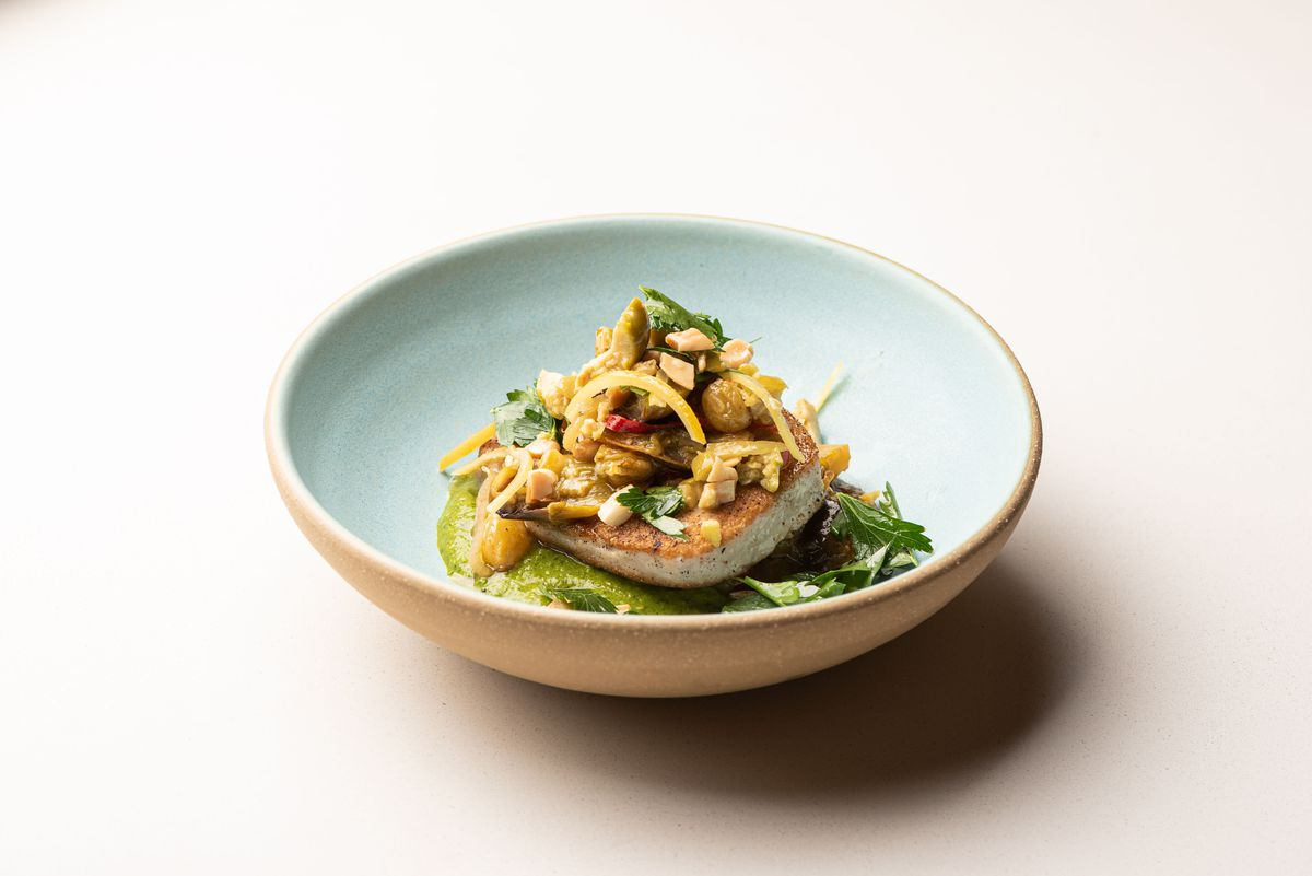 A light blue bowl hides a side of fish with crispy skin.