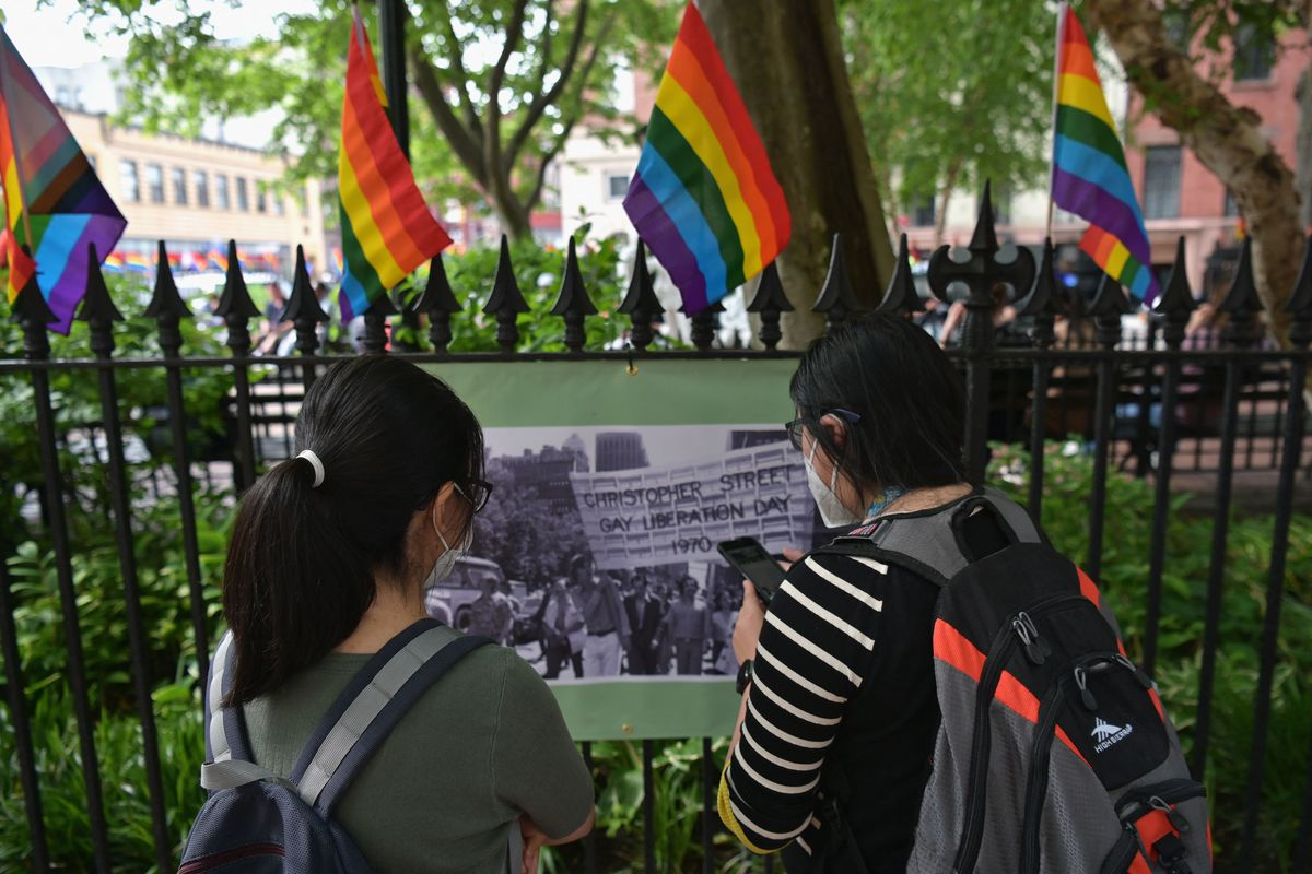 Two young women look at a historical photograph outside of the Stonewall National Monument in New York City, with Pride flags marking the top of a metal fence.