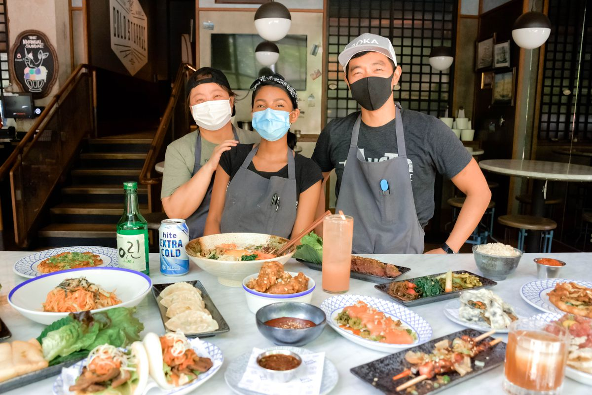 Three folks wearing masks in front of a table of food.