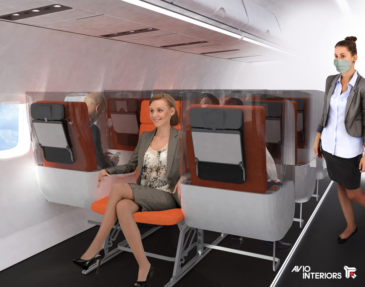 A woman sits in a middle airplane seat that's been turned around so that she's facing the back of the plane.