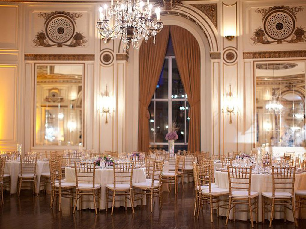 The interior of the Colony Club in Detroit. There are many tables and chairs, a chandelier, and a tall window with drapes.
