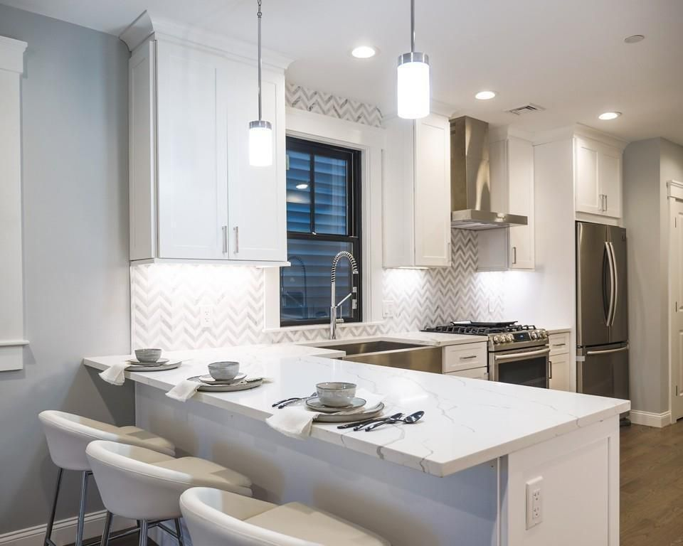 A kitchen with a counter jutting out and stools in front of that.