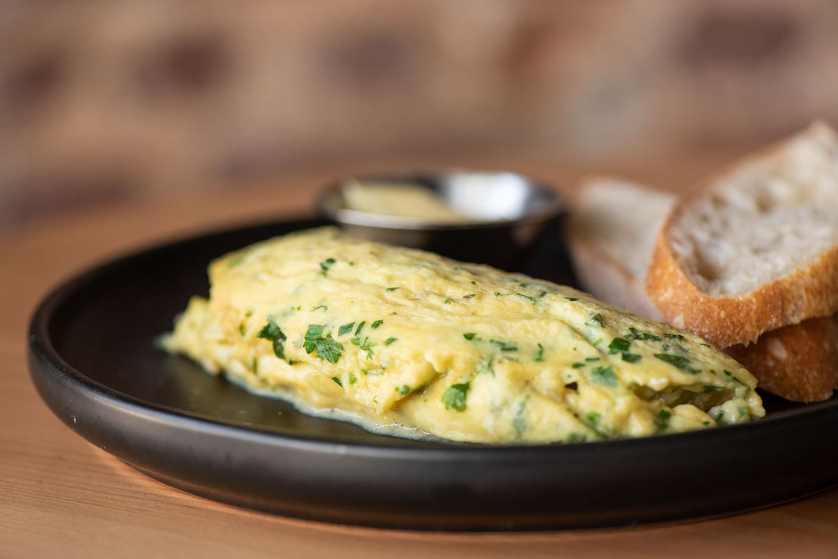 A buttery omelette with herbs on a black plate.