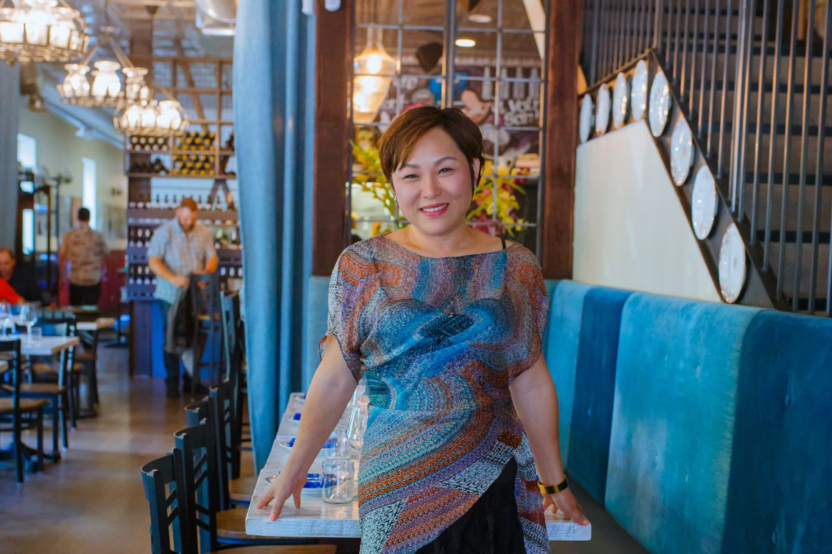 A woman in a colorful dress stands inside a restaurant with wooden floors.