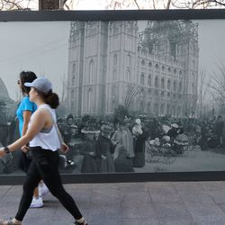 Pedestrians walk past a historical photo near Temple Square during the 191st Annual General Conference of The Church of Jesus Christ of Latter-day Saints in Salt Lake City on Saturday, April 3, 2021.