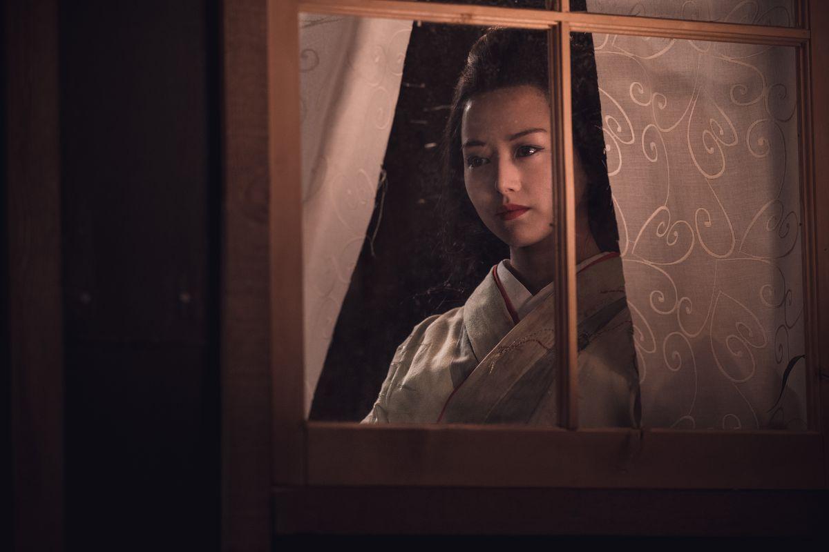 Yuko peeks through a window.