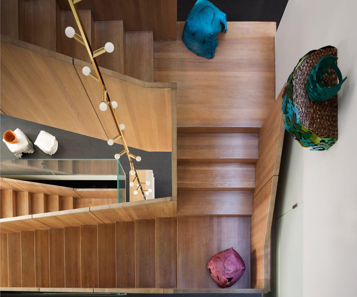 A top down view of a wooden staircase and a tall light fixture. There are various art objects arranged along the staircase and on the walls.