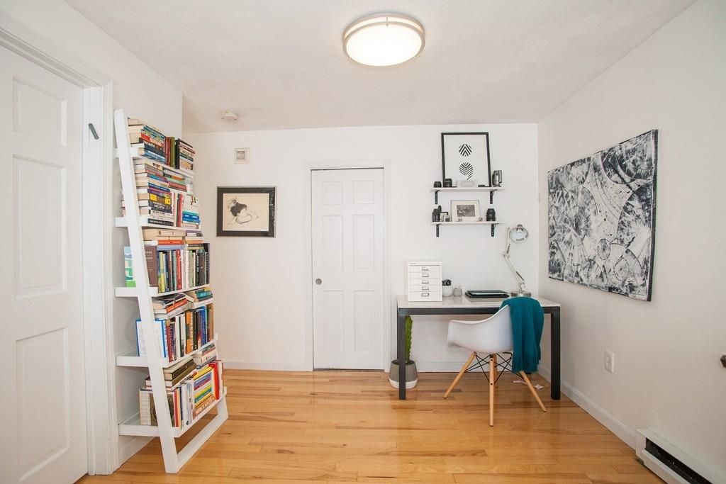 A room with a desk and a chair and some shelves with books next to them.