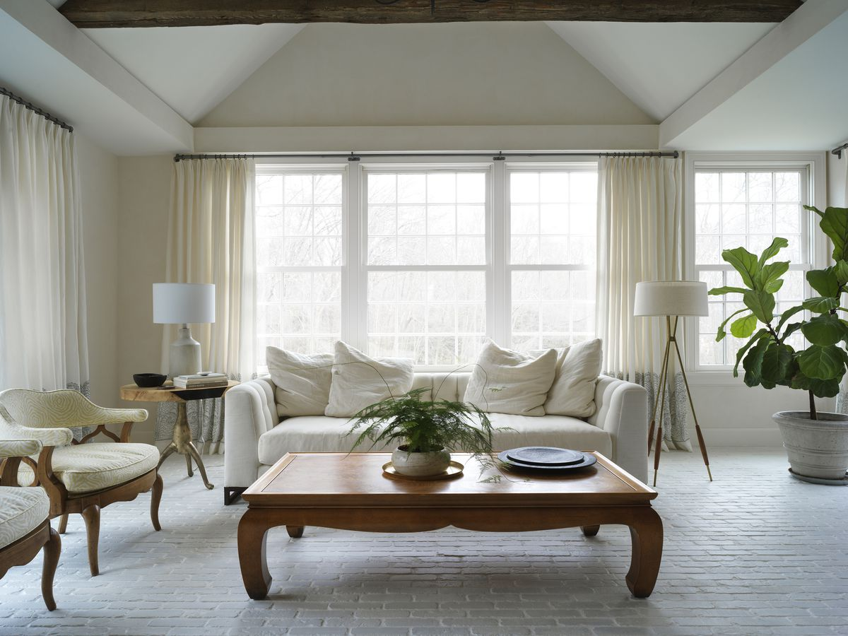 A living room has a low wooden coffee table and cream-colored sofa.