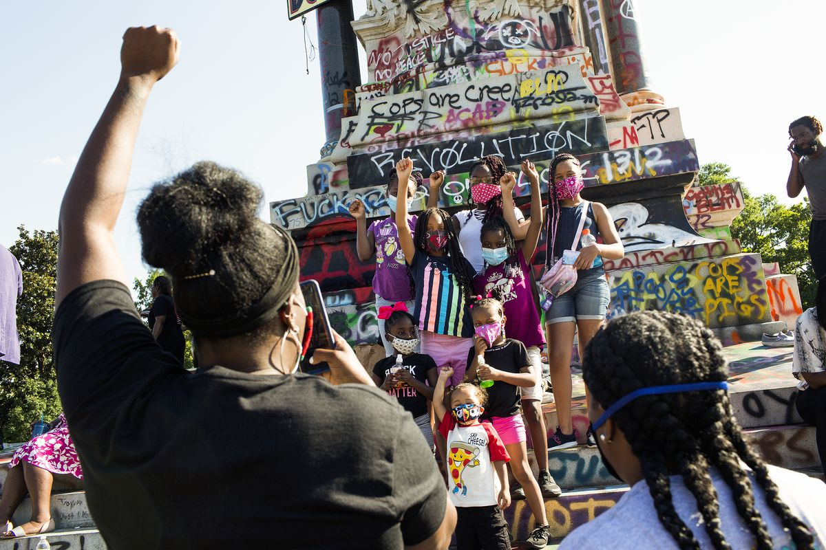 Protesters raise their fists in front of a graffiti-covered statue depicting Confederate General Robert E. Lee. The graffiti contains pro-BLM messages and calls for defunding the police.