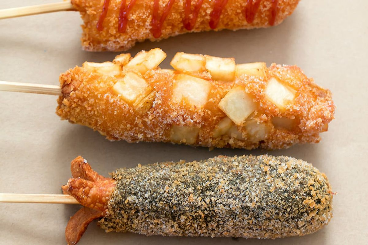 Three fried hot dogs on a stick, one covered in red sauce, one covered in cubes for fried potato, and one covered in a black seasoning.