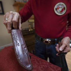 Eighty-seven-year-old retired Marine John Cole, who served and was wounded in North Korea, shows a knife like the one he used in battle at his home in Roy Wednesday, Feb. 18, 2015.