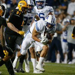 Brigham Young running back Lopini Katoa, center, runs under pressure during an NCAA college football game against Arizona State at LaVell Edwards Stadium in Provo on Saturday, Sept. 18, 2021.