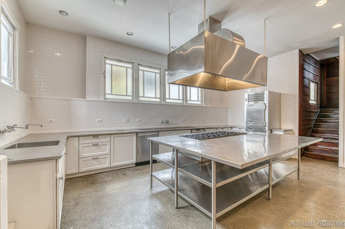 A large kitchen with white tilework and a massive stainless steel island with a steel hood above a huge ten-burner range.